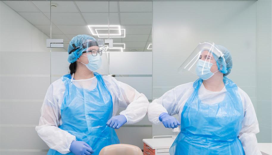 Odontologijos klinikos darbuotojai su kaukėmis